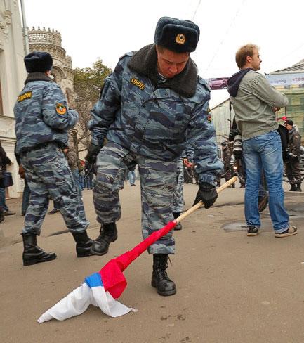 ОМОНовец ломает древко российского флага